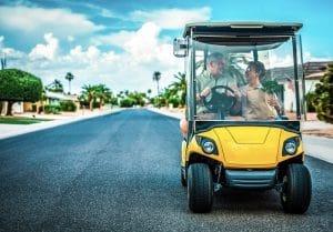 senior couple driving a golf cart