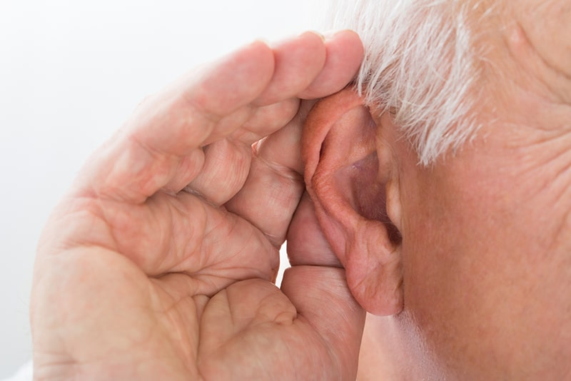 man cupping hand over ear to hear